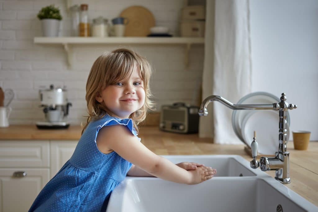 charming little girl blue dress washing hands kitchen cute female kid looking smiling camera helping mother doing dishes standing sink kids childhood cooking housework scaled