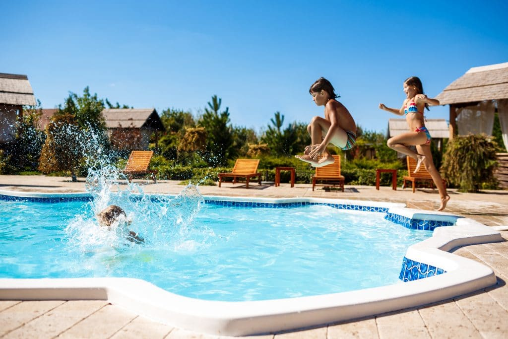 cheerful children rejoicing jumping swimming pool scaled