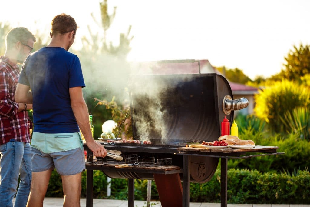 young men roasting barbecue grill cottage countryside scaled